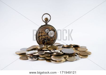 Old Clockwork with open cover on scattered coins isolated on white.Time is money concept.