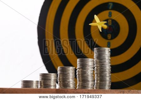 Yellow dart hit in the center of a target with stack of coins on white background with copy space. A idea about money / currency investment that must decide or think carefully.Copy space.