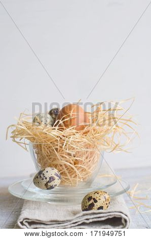 Easter Chicken And Quail Eggs In A Glass Cup On Gray And White Background