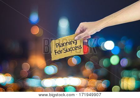Hand Holding A Planning For Success Made On Sugar Paper With City Light Bokeh As Background