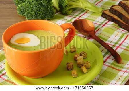 Cream soup of broccoli with egg and croutons in orange cup. Lunch meal. Vegetable soup in an orange cup. Checkered tablecloth