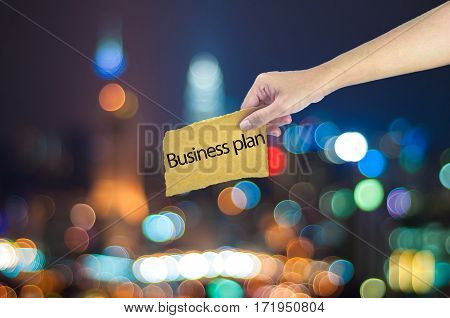 Hand Holding A Business Plan Sign Made On Sugar Paper With City Light Bokeh As Background