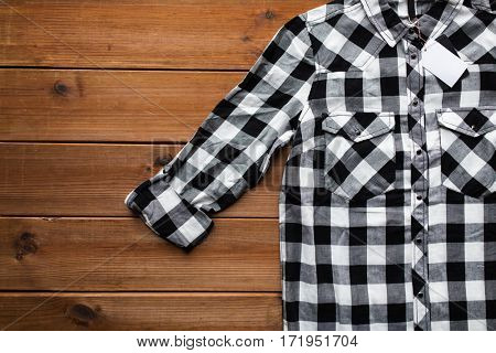 clothes, fashion and objects concept - close up of checkered shirt with price tag on wooden background