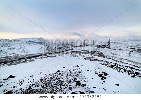 Steel works, smoking factory pipes. Winter landscape Arctic tundra