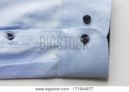 clothing, formal wear, fashion and objects concept - close up of blue shirt sleeve
