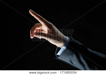 business, people and choice concept - close up of businessman hand pointing finger to something invisible over black background