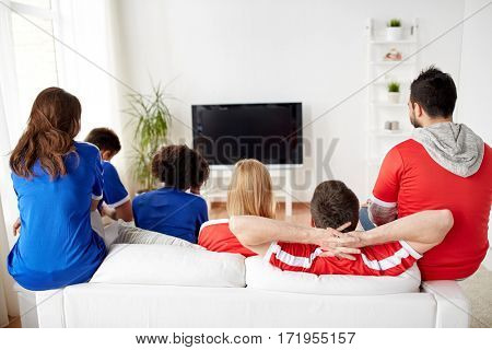 friendship, leisure, sport, people and entertainment concept - happy friends or football fans watching soccer on tv at home