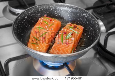 Cooking salmon fish fillet on frying pan