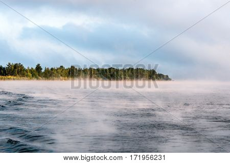 Morning on the lake. On the water surface trace of the ship.