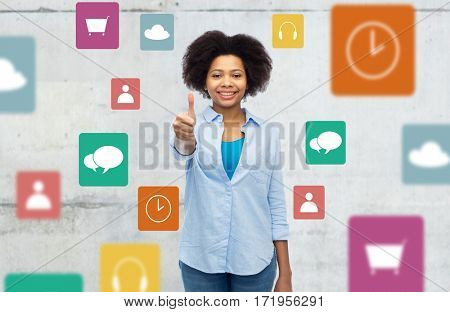 people, media and gesture concept - happy afro american young woman showing thumbs up over gray background with menu icons