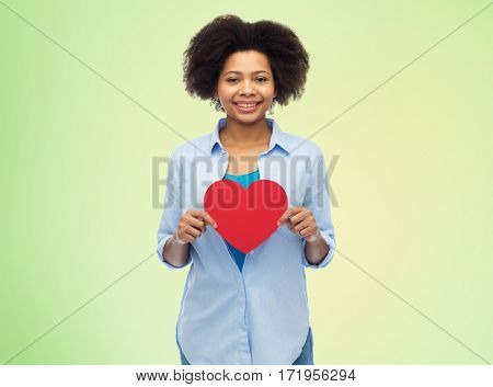 people, love, valentines day and health concept - happy african american young woman with red heart shape over summer green lights background