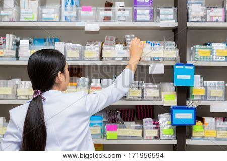 Asian woman a pharmacist in pharmacy room in hospital drug medicine Tablet capsule