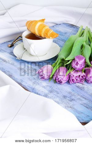 Morning breakfast with croissants cup of tea and purple tulips on blue wooden tray. Vertical orientation focus on tulips.