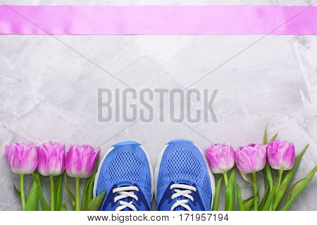 Spring flatlay sports composition with blue sneakers bottle of water and purple tulips on gray concrete background. Concept healthy lifestyle sport and diet in spring.