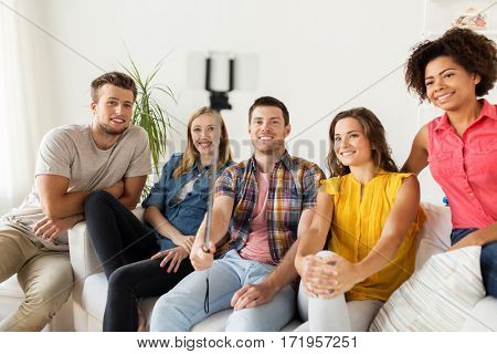friendship, and people concept - group of happy friends taking picture with smartphone and selfie stick at home