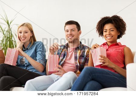 friendship, junk food, people and entertainment concept - happy friends eating popcorn and watching tv at home