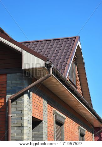 Attic with rain gutter and downspout pipe.