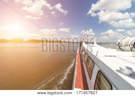 Walking tourist ship sails on the lake. The view from the deck of the ship. Sunny summer day.