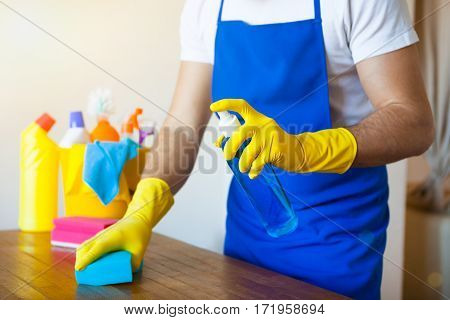 Closeup Of Young Man Wearing Apron Cleaning Kitchen Worktop set cleaning concept