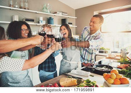 Group Of Friends Cheering At Kitchen.