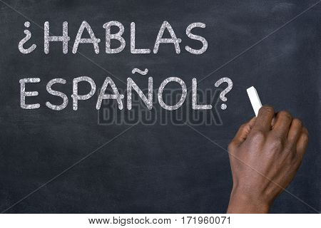 Question 'Hablas Espanol?' written on a blackoard