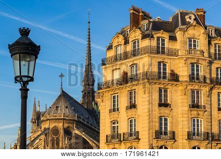 Haussmannian building facade on Ile de la Cite with Notre Dame Cathedral Spire and street lamp post. 4th Arrondissement Paris France