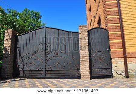 Outdoor house metal door gate installation. Metal door and gate exterior.