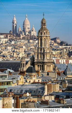 Rooftops of Paris with the Sacre Coeur Basilica in Montmartre and Trinity Church. 18th Arrondissement Paris France