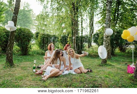 Five Girls Weared On White Dress On Hen Party Sitting Outdoor And Making Selfie At Park.