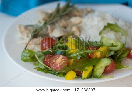 Fresh salad with cherry tomatoes arugula leaves cucumber and capsicum slices served with white rice and chicken slices
