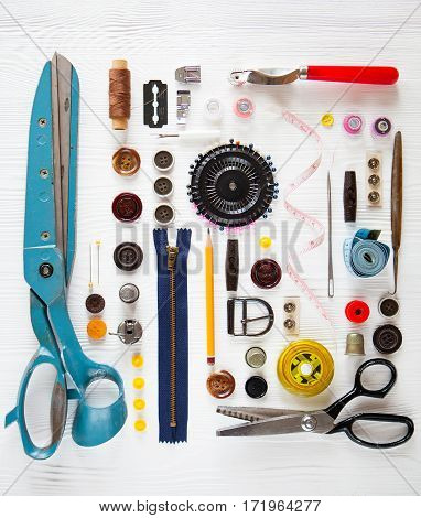 Flat Lay Of Sewing Tool And Accessories On White Wooden Background