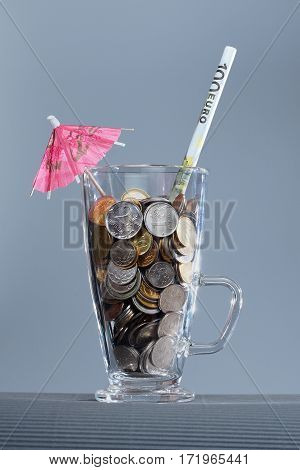 Shallow Russian coins in a glass. Cocktail straws from the euro and umbrella.