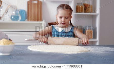 Little girls rolled pizza dough, cooking food