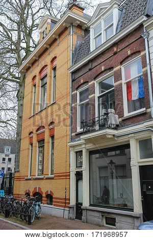 Utrecht the Netherlands - February 13 2016: Facade of old building with national flag behind window (Hamburgerstraat)