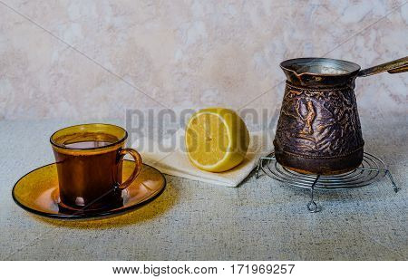 In a Cup of freshly brewed coffee next to a sliced lemon on the napkin and the pots on the makeshift stand: detail of some fan.