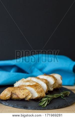 Vertical background with sliced chicken breast cooked with rosemary and served on small slate plate with blue napkin black background