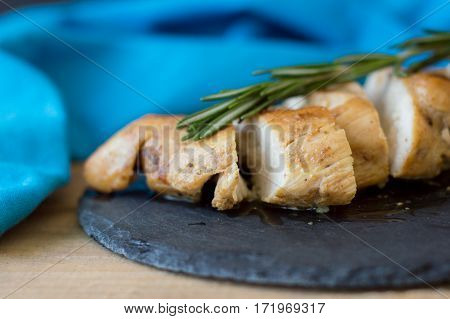 Slices of baked chicken breast served with green rosemary leaves on trendy black slate board with blue napkin selective focus