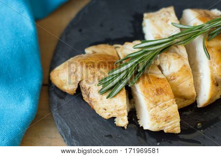 Top view of cooked chicken slices with fresh rosemary on black slate board and blue kitchen towel