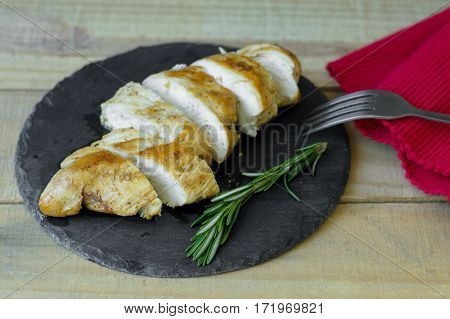 Portion of roasted chicken breast with fresh rosemary leaves served on black slate board with red napkin and metal fork on wooden table