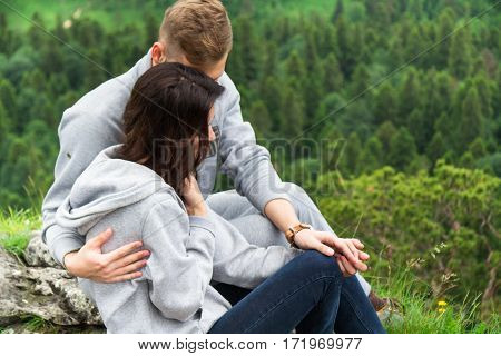 Happy Young Couple In Love Sitting On A Mountain, Hugging And Looking Away, Love And Feelings Concep