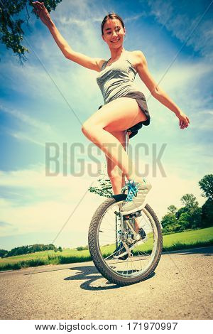 young athletic woman unicycling, having fun in the summer.