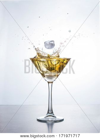 Yellow cocktail in martini glass with ice cube splashing into liquid against white background. Martini cocktail with splash on white background