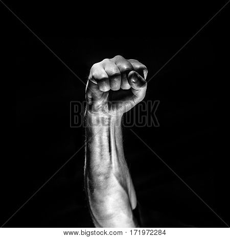 Strong Male Man Raised Fist On A Black Background, Power, War, Protest, Fist Ready To Fight
