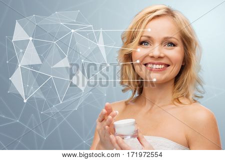 beauty, people, skincare and cosmetics concept - happy woman holding moisturizer jar over gray background with low poly projection and pointers