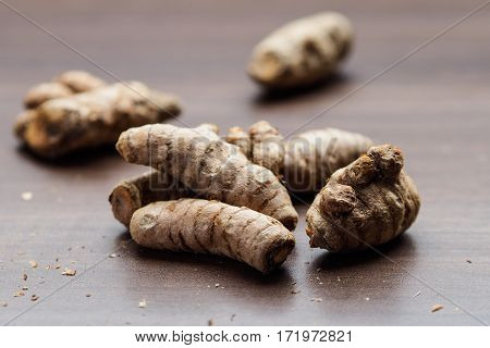 Raw turmeric roots on wood talbe background