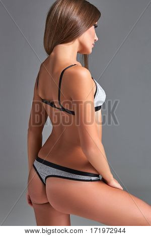 Beautiful girl in sports underwear isolated on gray background. Underwear gray color. Young woman standing with her back to the camera
