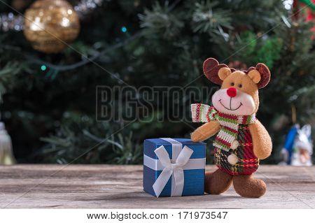 Happy reindeer standing near Christmas present box