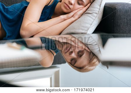 Closeup of exhausted lovely young woman lying and sleeping at home