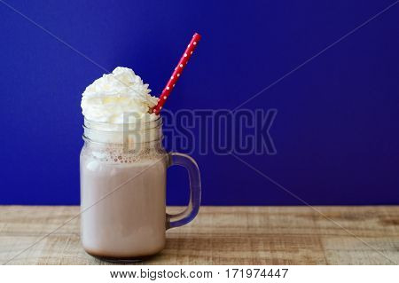 Portion of hot chocolate with white whipped cream in a glass jar with red paper straw blue background wooden table