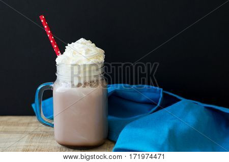 Glass with hot chocolate with whipped cream topping and red party straw on wooden table with blue kitchen towel black background